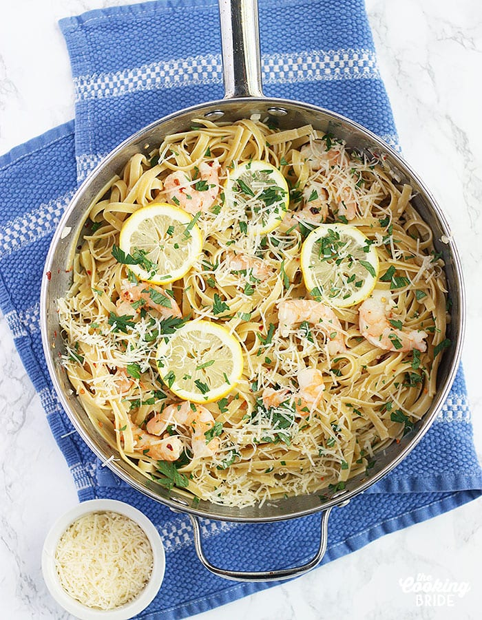 Fettuccine noodles topped with shrimp scampi in a stainless steel pan