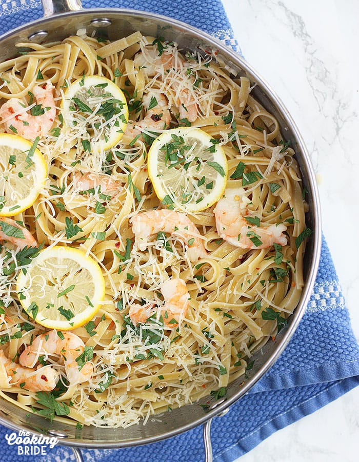 finished easy shrimp scampi in a stainless steel skillet topped with cheese and lemon slices