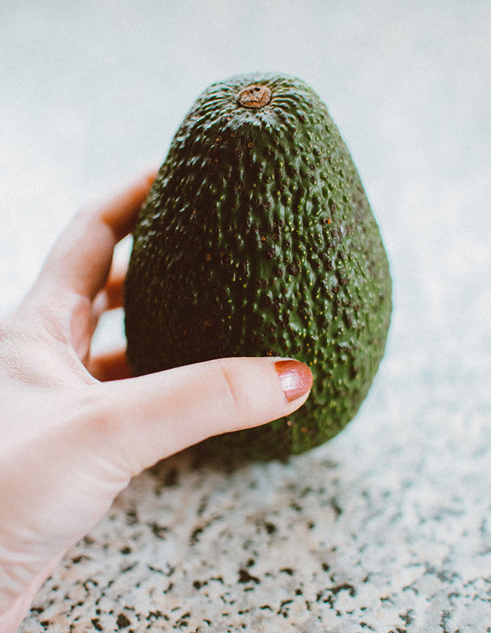 lady's hand holding an avocado upright on a countertop