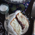 This beautiful and easy coconut cake is perfect for a holiday or Easter celebration. Two moist white cake layers are filled with raspberry preserves then iced with a simple coconut spread.