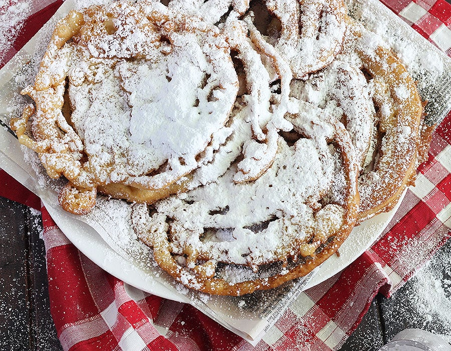 funnel cakes covered in powdered sugar on a red napkin