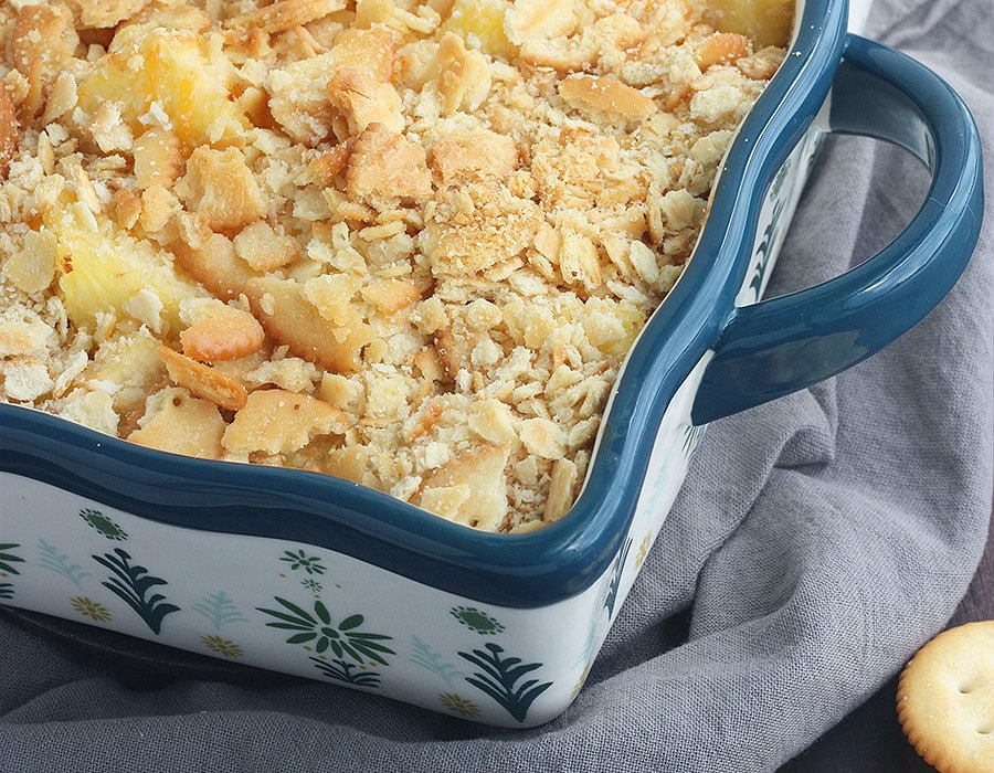 baked pineapple casserole with Ritz cracker topping in a blue and white casserole dish