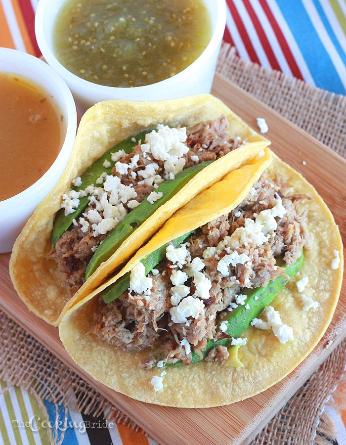 Pork shoulder is braised in onion and spices, then shredded and served on a corn tortilla with sliced avocado and queso fresco for a delicious pulled pork carnitas recipe.