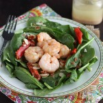 Succulent grilled shrimp salad is served over a bed of crisp fresh spinach leaves and drizzled with a vinegar based hot bacon dressing.