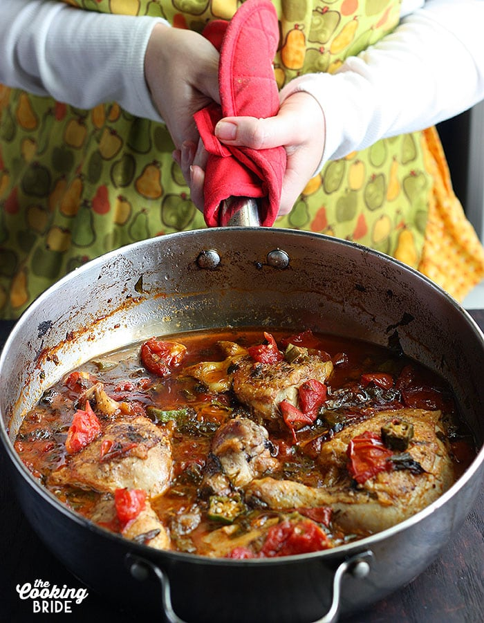 person holding a skillet of baked chicked with okra and tomatoes