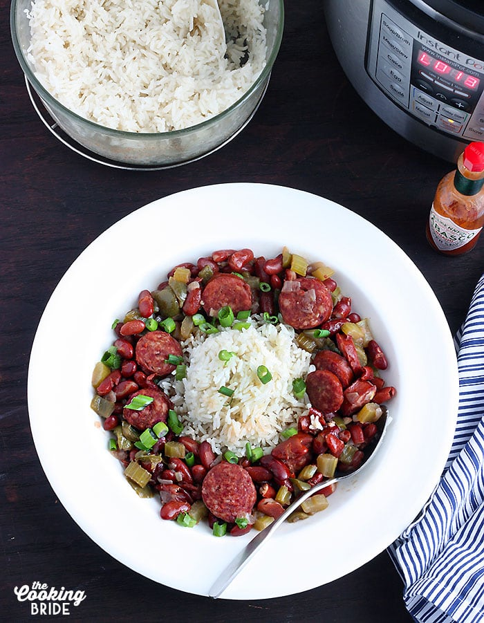 overhead shot of red beans and rice in a white bowl with rice, hot sauce and Instant Pot to the side