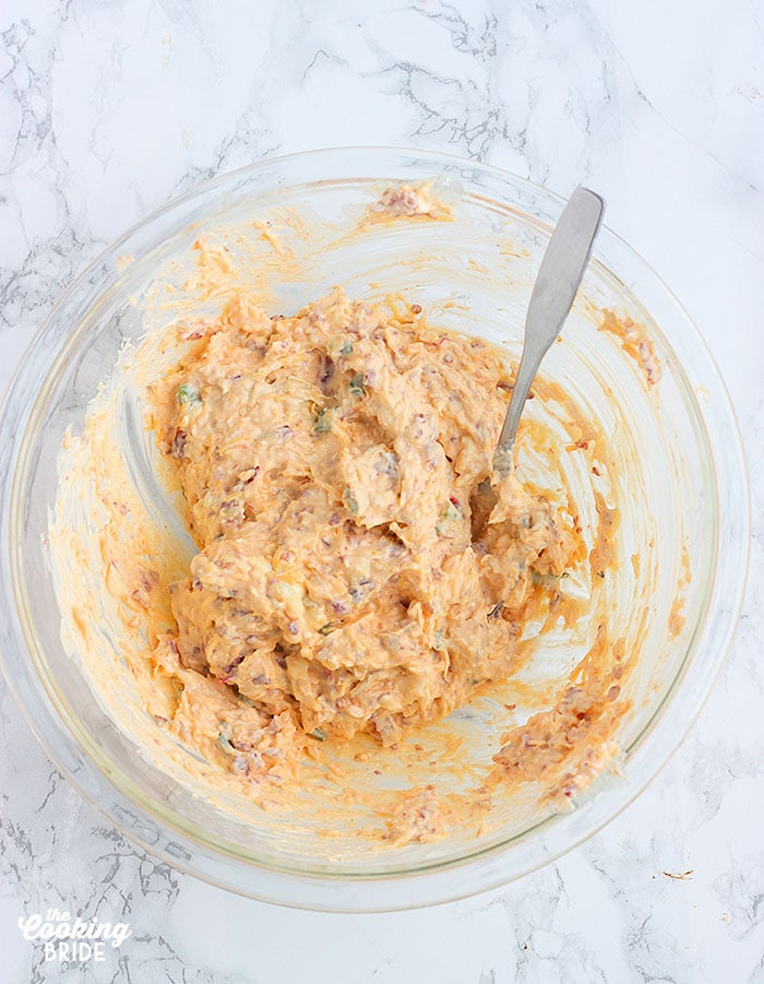 glass bowl of pimento cheese and a silver spoon on a marble backgroun