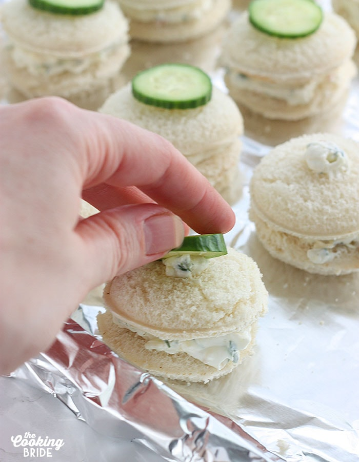 topping each sandwich with a slice of cucumber