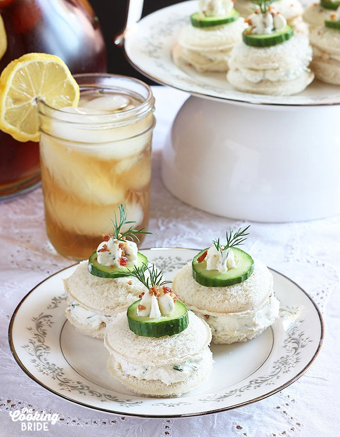 Three cucumber tea sandwiches on a white China plate with iced tea in the background