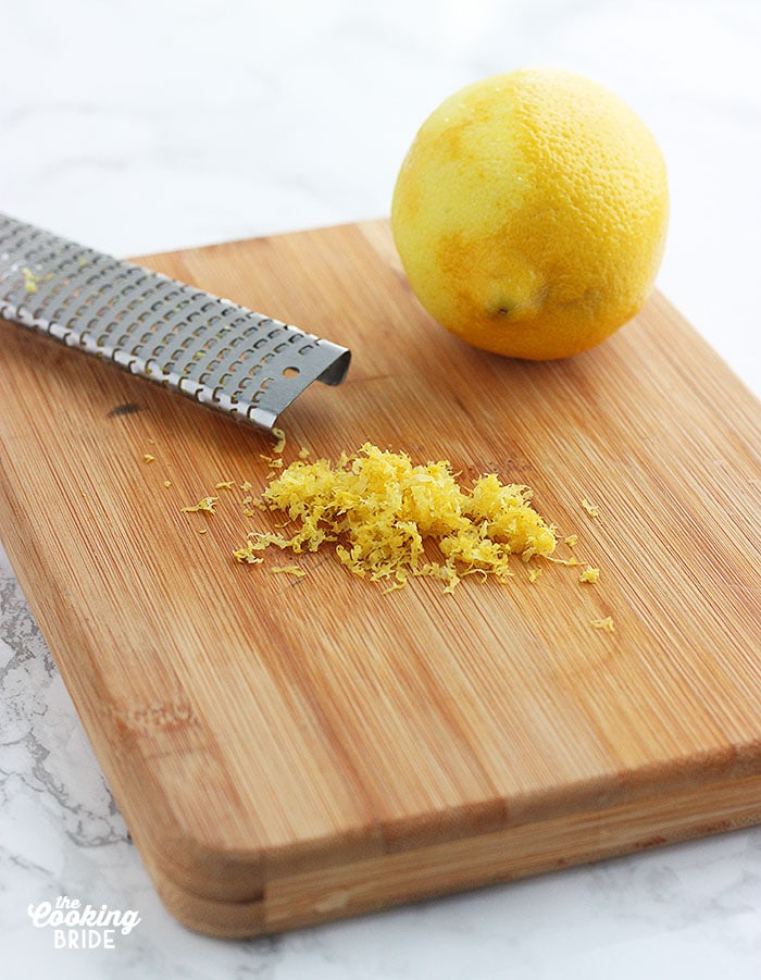 whole lemon and zest laying on a wooden cutting board