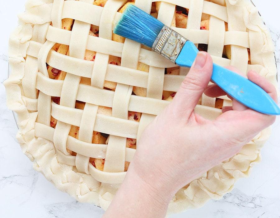 brushing egg wash on the lattice pie crust