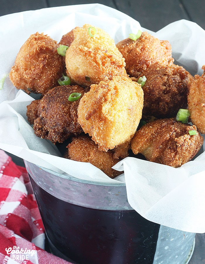pile of hush puppies in a metal bucket lined with white tissue paper