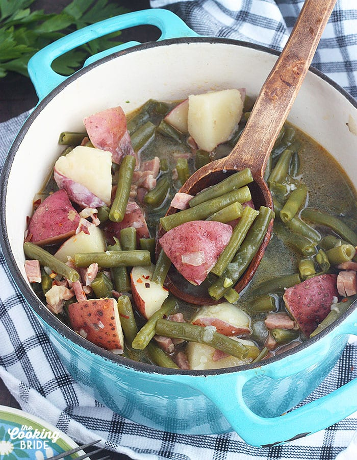 blue pot full of green beans and potatoes being served with a wooden spoon