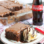 slice of coca cola cake on a white plate with a bottle of soda and the pan of cake in the background