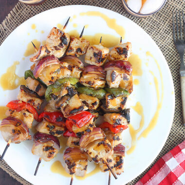 grilled pork skewers on a white platter drizzled with bourbon glaze